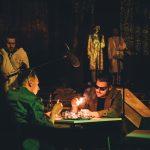 """Spektakl """"Popiół i diament – zagadka nieśmiertelności"""". Albert Pyśk (z lewej) w roli Maćka Chełmickiego i Mateusz Krzyk jako Andrzej Kossecki przywołują słynną z filmu Andrzeja Wajdy scenę płonących kieliszków. Fot. Karol Budrewicz"""